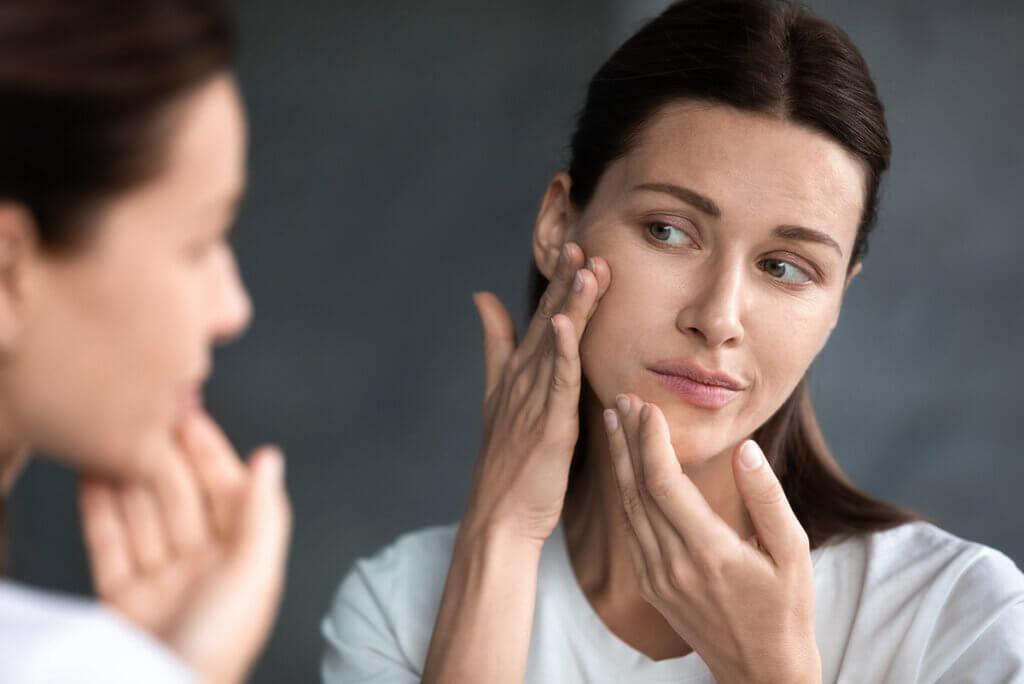 Kobieta oglądająca swoją cerę w lustrze